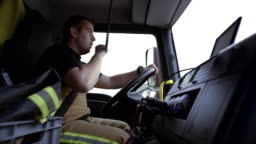 Firefighter driving a fire engine to the scene and communicating over the CB radio