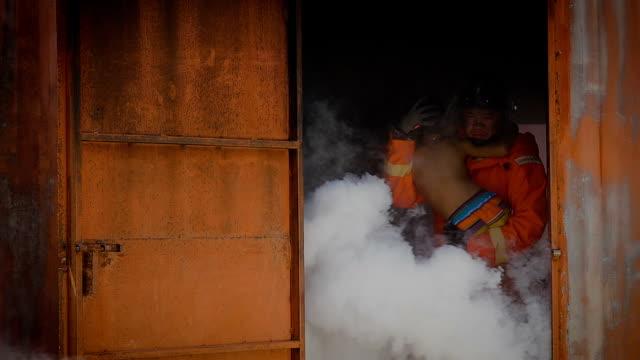 Feuerwehrmann, verletzt Feuerwehrmann hilft jungen um ihn zu retten aus der Verbrennung von Lager
