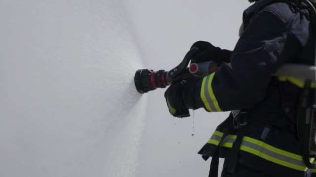 firefighter fireman using fire hose to bursting out water - fire hose stock videos & royalty-free footage