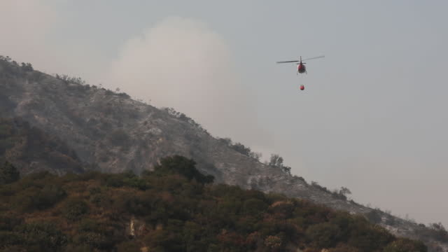 firefighter helicopter moving towards wildfire area. bobcat fire in angeles national forest. the u.s. west is bracing for another blast of dry and... - sierra madre stock-videos und b-roll-filmmaterial