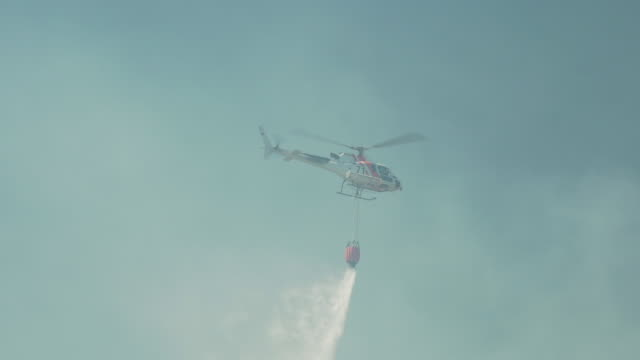 firefighter helicopter throwing water to put out the fire - emergency equipment stock videos & royalty-free footage