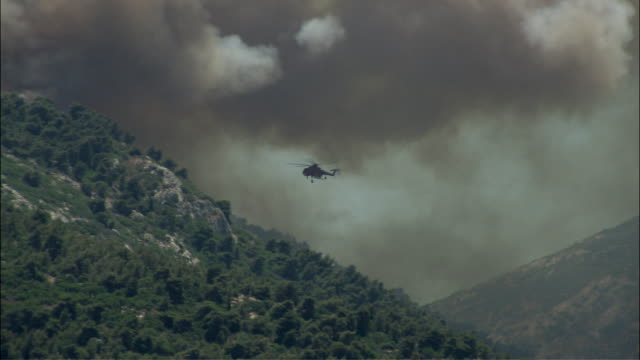 vídeos de stock e filmes b-roll de ws pan firefighter helitack flying over mountain and spraying water on forest fire / athens, attika, greece - athens greece