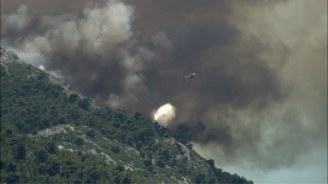 WS PAN Firefighter helitack flying over mountain and spraying water on forest fire / Athens, Attika, Greece