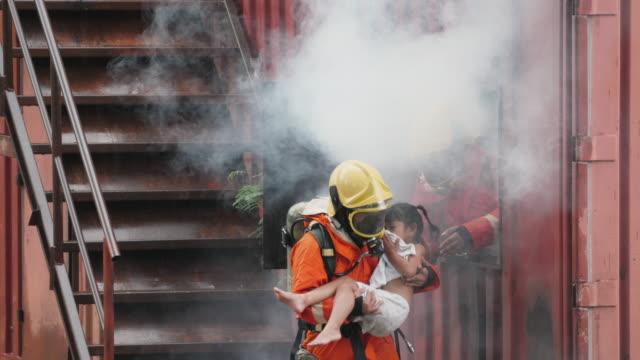vidéos et rushes de héros de pompier portant la petite fille hors de la zone brûlante de bâtiment - pompier