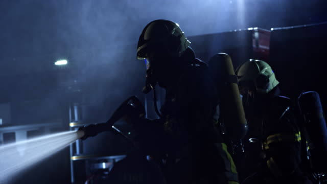 firefighter holding a hose and drenching the burnt out vehicle at night - fire hose stock videos & royalty-free footage