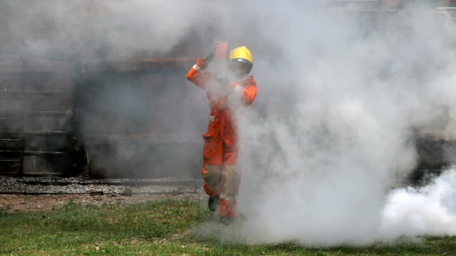vídeos de stock e filmes b-roll de firefighter holding fire hose and running through smoke to extinguish a fire - bombeiro