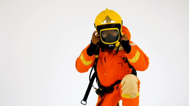 firefighter man in in orange fire-proof uniform wearing hat and mask over white background - firefighter stock videos & royalty-free footage