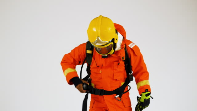 firefighter man in in orange fire-proof uniform wearing hat and mask over white background - uniform stock videos & royalty-free footage