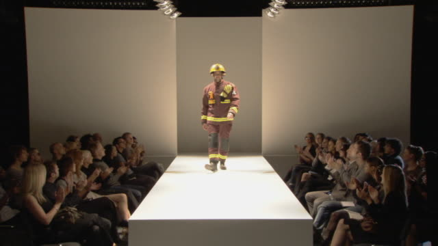 ws firefighter modeling on catwalk while audience applauds / london, england, uk - catwalk stock videos & royalty-free footage