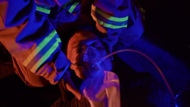 feuerwehrmann platzierung nicht rückatmung maske auf dem gesicht eines männlichen feuer-unfall in der nacht - todesopfer stock-videos und b-roll-filmmaterial