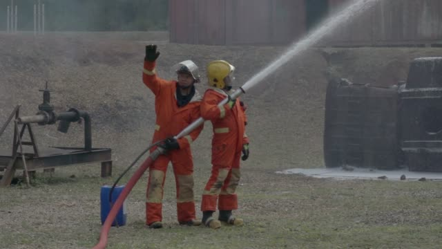 stockvideo's en b-roll-footage met brandweerman praktijk slowmotion - fire hose