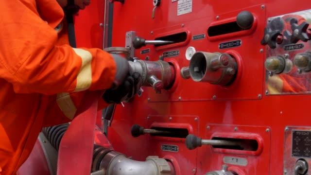 stockvideo's en b-roll-footage met brandweerman praktijk met vrachtwagen - helm apparatuur