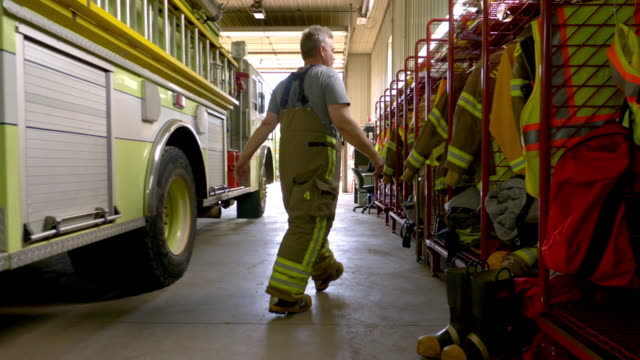 firefighter putting on coat - fire station stock videos & royalty-free footage