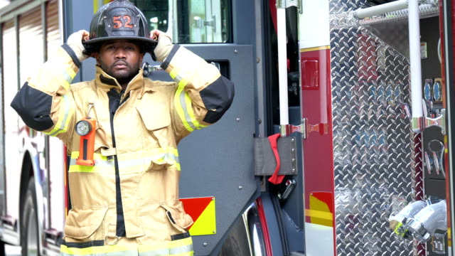 firefighter putting on fire protection suit and helmet - fire station stock videos & royalty-free footage