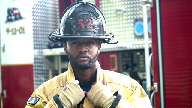 firefighter putting on helmet - helmet stock videos & royalty-free footage
