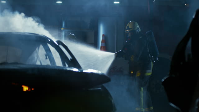 slo mo firefighter putting out a car caught on fire with water gushing out a fire hose - fire hose stock videos and b-roll footage