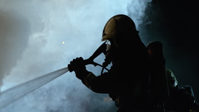 vídeos de stock e filmes b-roll de slo mo firefighter putting out a fire at night - bombeiro