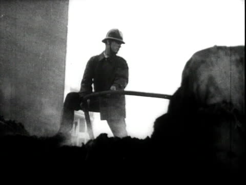 vidéos et rushes de firefighter putting out fires in the rubble caused by fascist bombing / destruction of buildings and bombed tram / excavating the dead from the rubble - bombardement