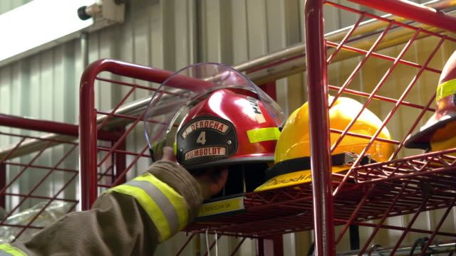 a firefighter reaches for his fire helmet responding to an emergency call - fire station stock videos & royalty-free footage