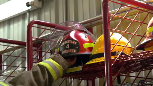 vídeos y material grabado en eventos de stock de a firefighter reaches for his fire helmet responding to an emergency call - parque de bomberos