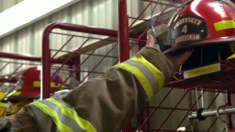 a firefighter reaches for his fire helmet responding to an emergency call - firefighter stock videos & royalty-free footage