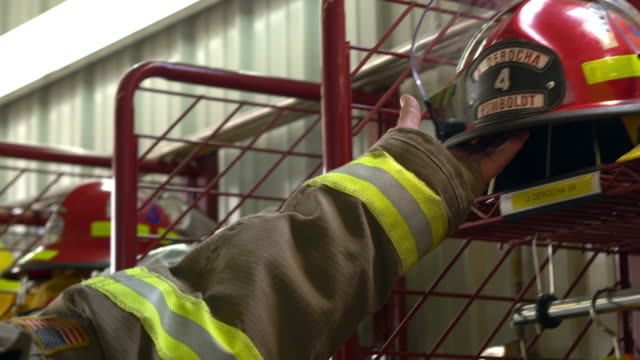 vídeos de stock, filmes e b-roll de a firefighter reaches for his fire helmet responding to an emergency call - cultura americana