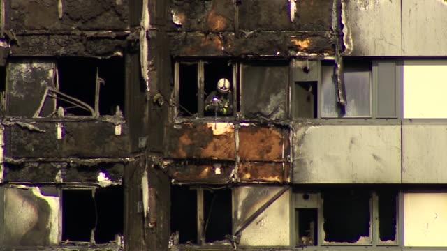 vídeos de stock, filmes e b-roll de a firefighter removing material from the outside of grenfell tower - armação de janela