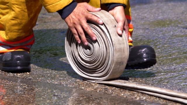 stockvideo's en b-roll-footage met 4k rt brandweerman rolwerk brand slang op de grond. - fire hose