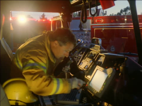 ms firefighter sitting in fire truck typing on computer + talking into walkie talkie - vigile del fuoco video stock e b–roll