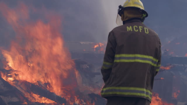a firefighter sprays water on flames blazing above rubble from a house fire - myrtle creek stock videos and b-roll footage