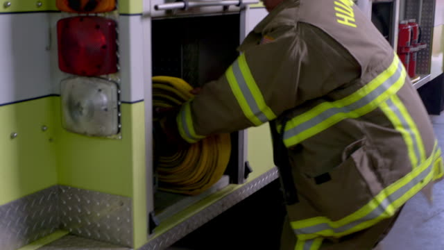 A firefighter stores firehose line and equipment on the fire truck at the station