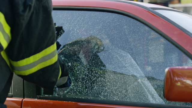 Firefighter using a window breaking tools to shatter glass and remove it