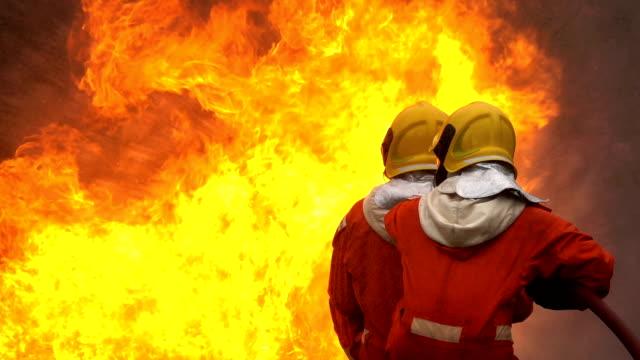 feuerwehr löscht mit feuerwehrschlauch einen brand im brennenden gebäude - fire hose stock-videos und b-roll-filmmaterial