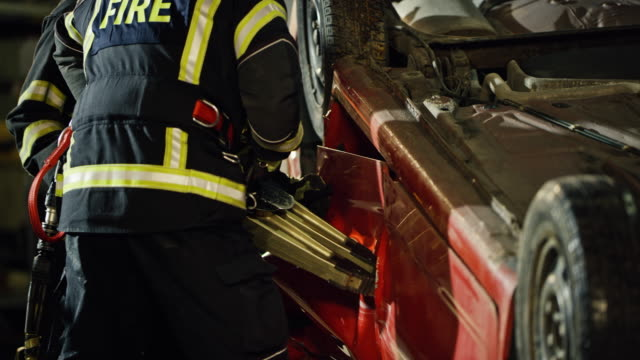 firefighter using the hydraulic spreaders to open the door of a car turned over in an accident - traffic accident stock videos & royalty-free footage