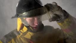 Firefighter walking towards camera through smoke, slow motion