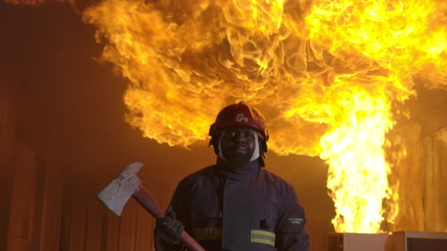 firefighter working. fire is raging. in slow motion. - firefighter stock videos & royalty-free footage