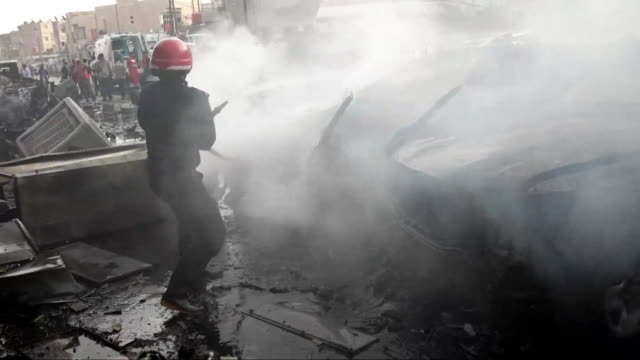 firefighters and civilians attempting to put out fires after an isis car bomb attack in qamishli syria - syria stock videos & royalty-free footage