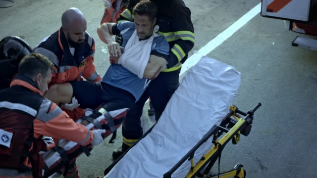 firefighters and paramedics lifting the injured male cyclist onto the stretcher at the scene of the accident - rescue worker stock videos & royalty-free footage