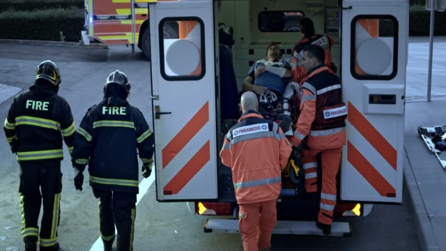 firefighters and paramedics pushing the stretcher with an injured male cyclist into the ambulance - stretcher stock videos & royalty-free footage
