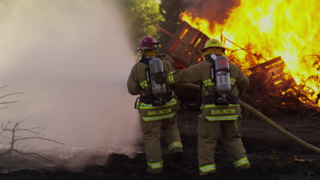 Firefighters approach a flaming bonfire armed with a firehose spraying water.