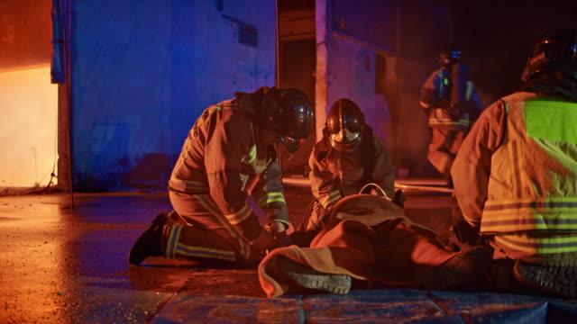 消防士夜火災現場で地面に横たわって火災死傷者を支援 - 空気弁点の映像素材/bロール