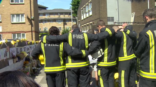 Firefighters at the scene of Grenfell Tower observing a minutes silence for the victims before being applauded for their efforts by residents and...