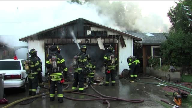 firefighters battle a house fire in sacramento on july 30, 2013 in sacramento, california - fire protection suit stock videos & royalty-free footage