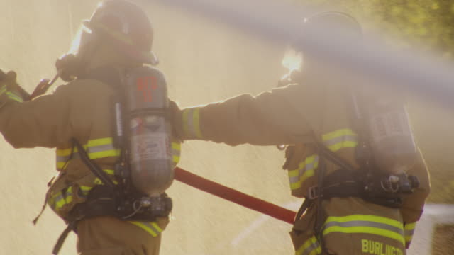 vídeos de stock e filmes b-roll de firefighters battle a roaring blaze, spraying water from firehoses. - bombeiro