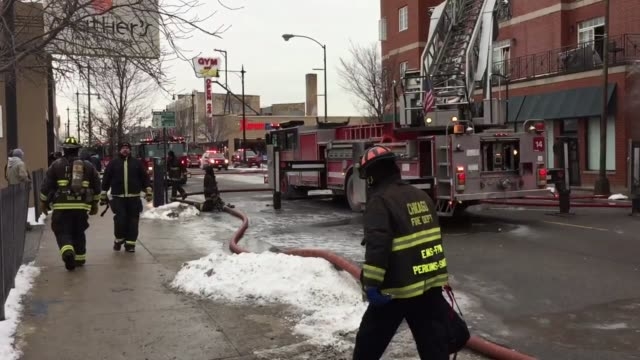 firefighters battled an extra alarm fire near belmont and central avenue in chicago on wednesday afternoon. water can be seen pouring from windows as... - fire protection suit stock videos & royalty-free footage