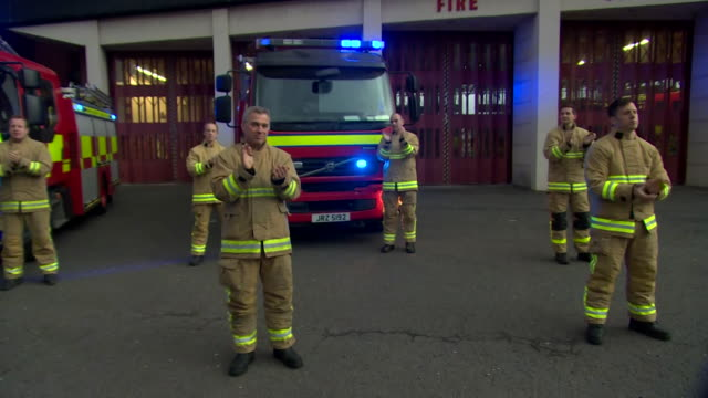 firefighters clapping and cheering for the nhs and all keyworkers during the clap for carers event during the coronavirus - nhs stock-videos und b-roll-filmmaterial