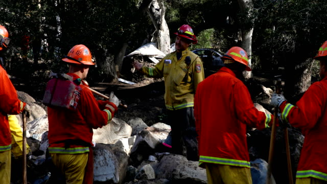 Firefighters clear debris from a mudslide as they try to fix a gas leak on January 10 2018 in Montecito California 15 people have died and hundreds...