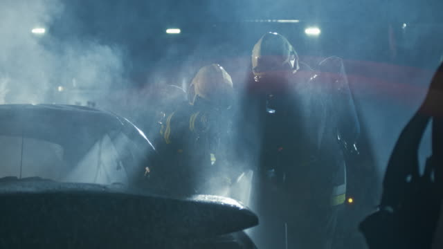 SLO MO Firefighters drenching a burnt out car with water after an accident at night