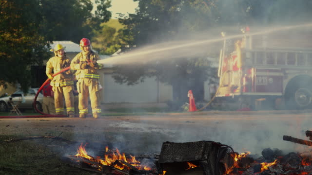 firefighters extinguish a bonfire and have it under control - hose stock videos and b-roll footage