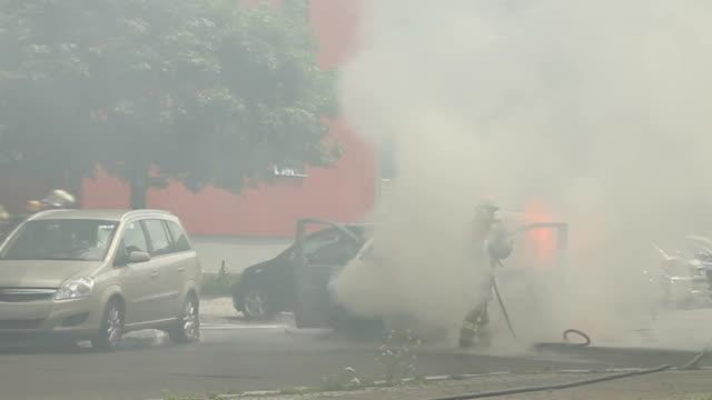 Feuerwehrleute Löschen einer brennenden Auto